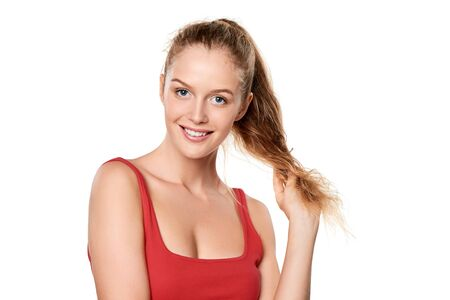 pony tail: Beauty portrait of young woman touching her pony tail hair, over white background