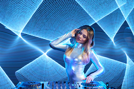 closed club: Beautiful DJ girl in silver overall playing mixing music on vinyl turntable at party over white led background