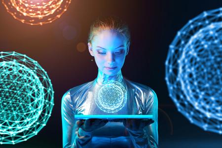 mujer joven futurista del cyber en la ropa de plata sosteniendo panel de iluminación en sus manos con la esfera abstracta poligonal brillante con esferas abstractas en el fondo