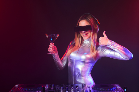 coverall: Happy DJ girl on decks at the party wearing silver coverall holding a glass with cocktail and gesturing thumb up Stock Photo