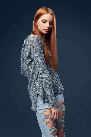 Red haired female fashion model wearing sweater and distressed jeans posing in studio