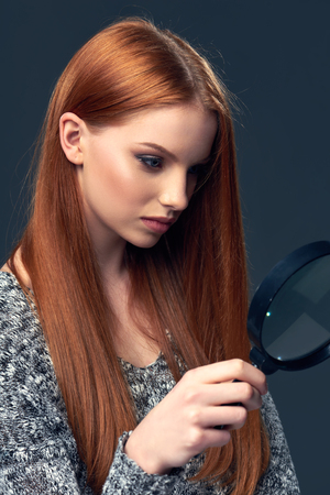 Beautiful red hair woman looking through magnifying glass