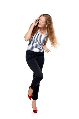 laugher: Full length portrait of young, happy laughing beautiful woman talking on cell phone showing yes gesture celebrating success, over white background