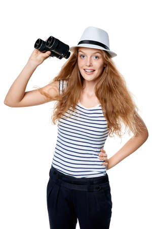 Young beautiful teen female in striped tee and white straw fedora hat holding binoculars and looking at camera smiling happy, over white background Stock Photo