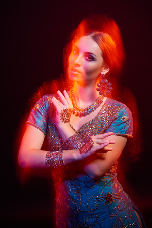 mixed marriage: Fine art portrait of beautiful fashion Indian woman with oriental dress, accessories- earrings, bracelets and rings and mehndi henna tattoos. Mixed lighting photography. Stock Photo
