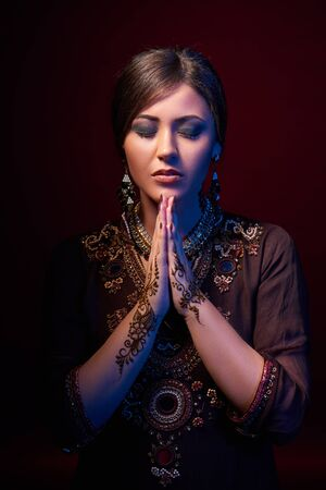 fine art: Fine art portrait of beautiful fashion Indian woman with oriental dress, accessories and mehndi henna tattoos with hands clasped together praying Stock Photo