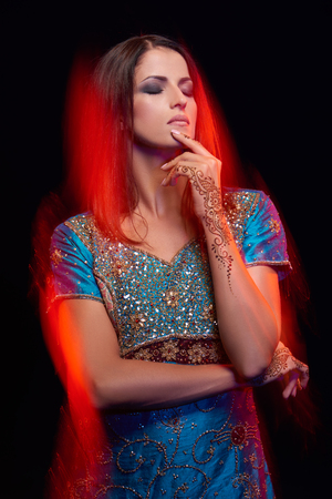 fine art: Fine art portrait of beautiful fashion Indian woman with oriental dress, accessories- earrings, bracelets and rings and mehndi henna tattoos. Mixed lighting photography. Stock Photo