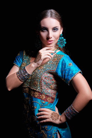 fine art: Fine art portrait of beautiful fashion Indian woman with oriental dress, accessories- earrings, bracelets and rings and mehndi henna tattoos.