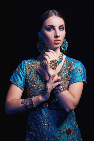 arab glamour: Fine art portrait of beautiful fashion Indian woman with oriental dress, accessories- earrings, bracelets and rings and mehndi henna tattoos.