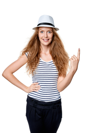 Happy summer woman in white straw fedora hat pointing her finger up