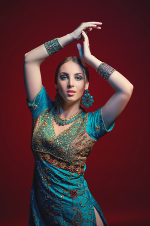 bracelet tattoo: Woman wearing traditional Indian sari with accessories- earrings, bracelets and rings and mehndi henna tattoos posing with hands raised