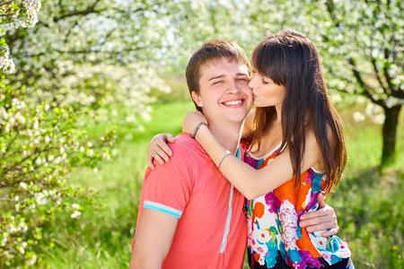 Young couple having fun hugging kissing in blooming garden