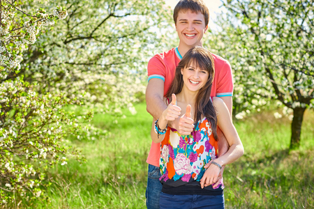Happy young couple enjoying hugging in blooming garden gesturing thumb up Stock Photo