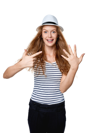 girl in a hat: Hand counting. Happy excited summer woman in straw fedora hat showing seven fingers. Girl showing five fingers and pointing at it with other hand. Stock Photo