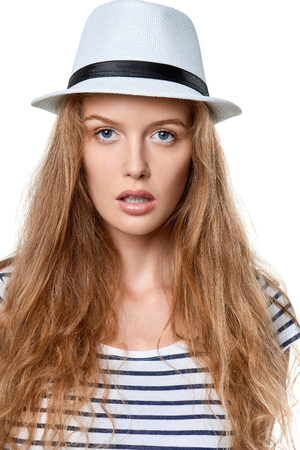 earnest: Closeup portrait of young woman in white straw hat staring at camera, over white background