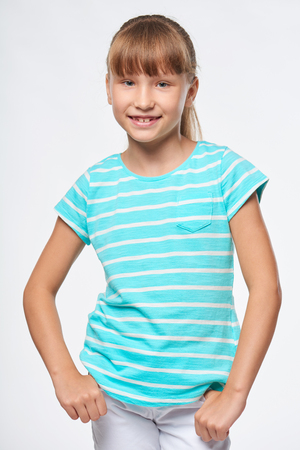 child smile: Smiling elementary school age girl standing relaxed with hands in pockets, over white background Stock Photo