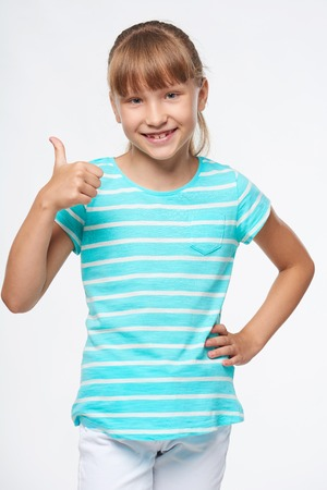 Sourire élémentaire fille d'âge scolaire debout gestes thumb up signe, sur fond blanc