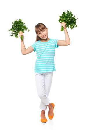 8 years: Happy smiling elementary school age girl standing in full length and showing fresh parsley, over white background