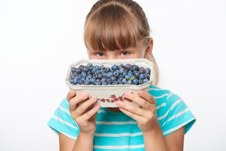 over white: Smiling girl holding a box with bilberries, over white background