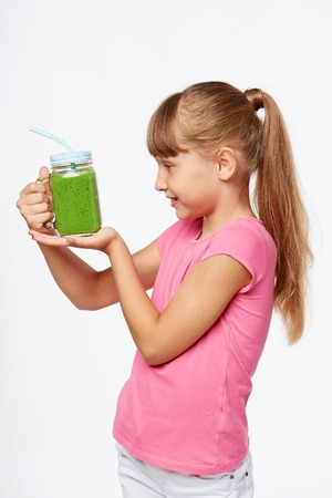 a jar stand: Side view of a girl holding jar tumbler mug with green smoothie drink, looking at it, over white background