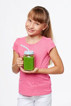 8 years: Happy smiling girl holding jar tumbler mug with green smoothie drink over white background Stock Photo