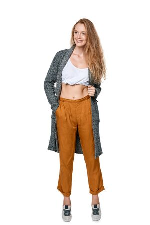 long pants: Trendy young woman in pants and long cardigan in full length smiling happy looking away, over white background Stock Photo