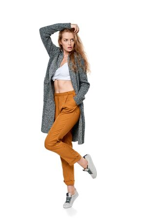 Trendy young woman in pants and long cardigan in full length posing looking away, over white background Stock Photo