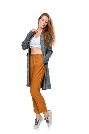 pantalones abajo: Mujer joven de moda en pantalones y chaqueta larga de longitud completa que presenta mirando hacia abajo, sobre el fondo blanco