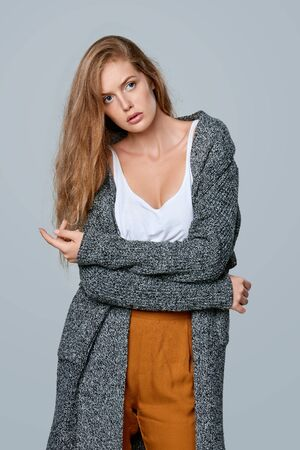 Fashionable beautiful woman in warm knitted cardigan, over gray background Stock Photo