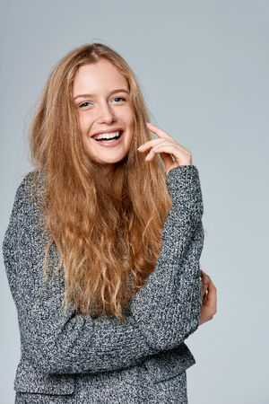Happy laughing beautiful woman muffling in warm knitted cardigan, over gray background
