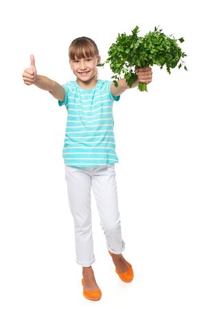Happy smiling little girl standing in full length, showing fresh parsley, and gesturing thumb up, over white background Stock Photo