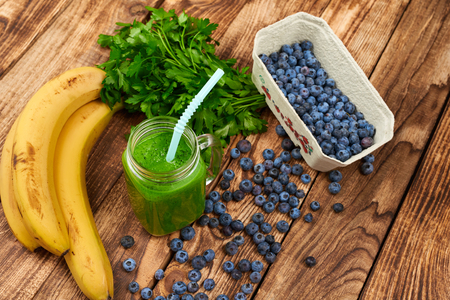Jar tumbler mug with green smoothie drink and a bundle of fresh parsley, banana and blueberries on wooden table Stock Photo