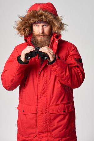 winter jacket: Portrait of a man wearing red winter jacket with fur hood on with binoculars, studio shot Stock Photo