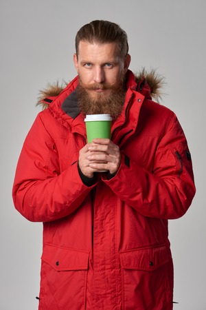 winter jacket: Portrait of a man wearing red winter jacket and holding hot drink in disposable paper cup, studio shot Stock Photo
