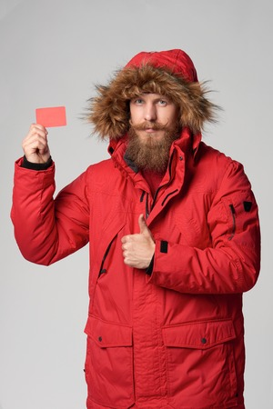 winter jacket: Portrait of a man wearing red winter jacket with hood on showing blank credit card and gesturing thumb up, studio shot Stock Photo