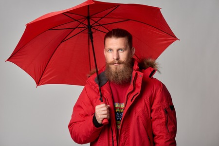 Portrait of bearded man in red winter jacket standing with umbrella, over grey background