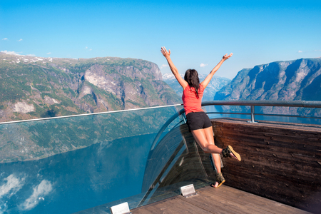 raised viewpoint: Joyful woman enjoying scenics from Stegastein Viewpoint in a summer sunny day , Flam, Norway