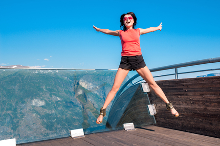 raised viewpoint: Excited emotional woman tourist at Stegastein Viewpoint jumping of joy with hands raised in a summer sunny day, Flam, Norway