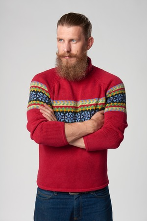 tog: Serious confident bearded hipster man in woolen sweater standing with folded hands and looking away out of frame, studio portrait over grey background