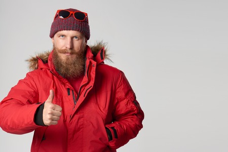 coincidir: Serious bearded man in red winter jacket showing thumb up gesture, over grey background