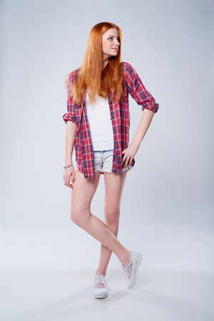 red haired girl: Full length beautiful red haired teen girl in plaid shirt and shorts looking to the side Stock Photo