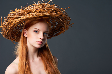 portait: Closeup of beautiful woman in natural wreath of wicker, studio portait with copy space