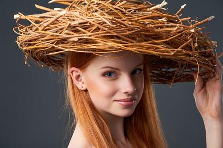 Closeup of smiling beautiful woman in natural wreath of wicker
