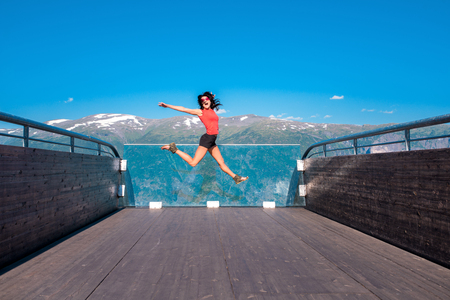 Excited emotional woman tourist at Stegastein Viewpoint jumping of joy with hands raised in a summer sunny day, Flam, Norway
