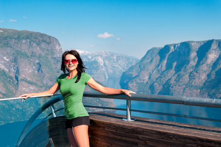 lookout: Woman tourist on Stegastein Viewpoint in a summer sunny day, Flam, Norway