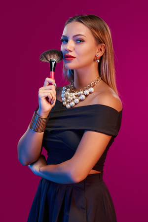 glamourous: Portrait of glamourous female makeup artist posing with brush