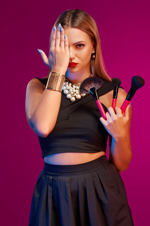 glamourous: Portrait of glamourous female makeup artist posing with brush covering one eye with her palm