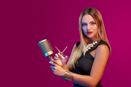 Portrait of glamourous female stylist posing with hairdresser's accessories