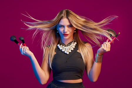 glamourous: Glamourous female stylist with hair flying holding makeup brushes