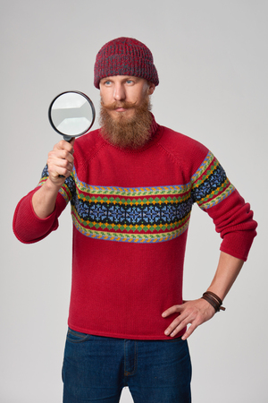 looking through: Search and idea concept. Man in a red winter sweater looking through magnifying glass